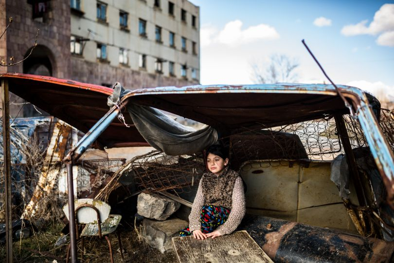 """Syuzanna (9) sitting in a """"shelter"""" made of old car rusty parts in front of the abandoned building she lives in Gyumri, Armenia. Ten days ago Syuzanna's father committed suicide, as people say, because of the debts 