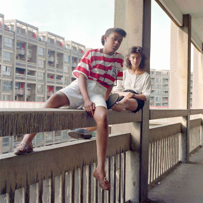 Bill Stephenson, Donna Hargreaves and Carmen Bello sit on an unguarded fourth storey concrete parapet. Hyde Park Flats, Sheffield, 1988 © Bill Stephenson