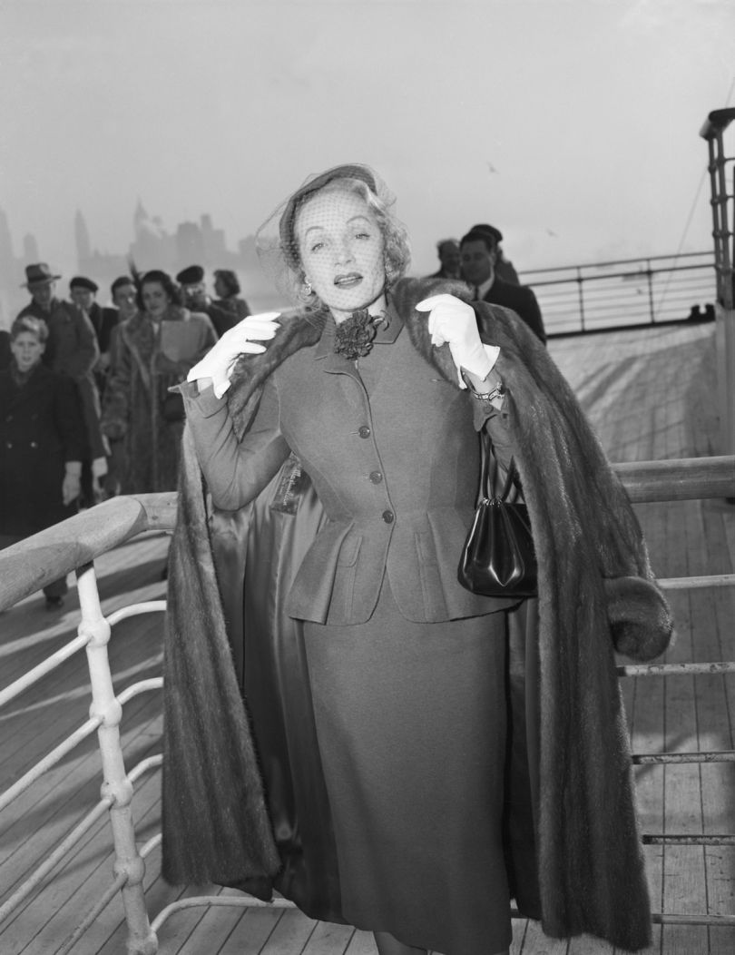 Marlene Dietrich wearing a day suit by Christian Dior on-board the Queen Elizabeth arriving in New York 21 December 1950 © Getty Images