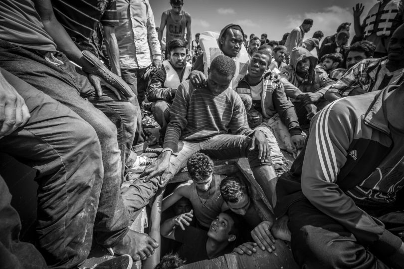 Onboard a fishing boat 30 miles off the coast of Libya, a Bangladeshi man begs to be released from the overcrowded hold of the boat where he was packed with 150 men in slaveship like conditions. The boat carried 414 migrants and refugees attempting to reach Italy. The migrant boat was intercepted by the NGO Migrant Offshore Aid Station's rescue ship, and all the people onboard were evacuated. © Jason Florio. Photojournalism Series Winner, Magnum and LensCulture Photography Awards 2017
