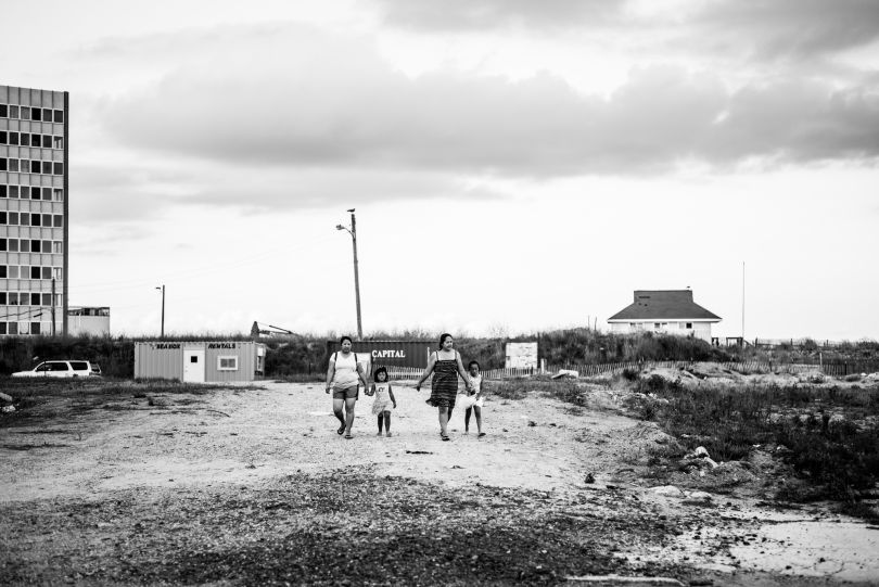 Mothers and daughters walk through the detritus of failed development. © Timothy Roberts