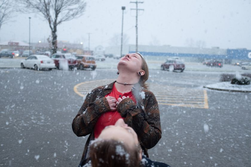 Allie and Regina catching snowflakes after a close friend's funeral. © Mark E. Trent