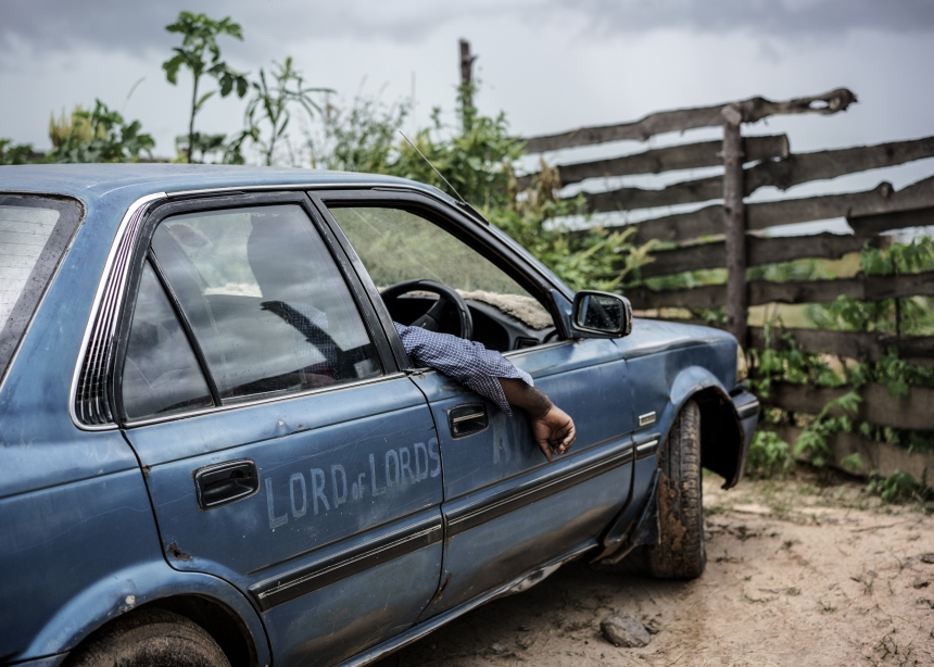 Much like the biblical Jesus was originally a carpenter, Jesus of Kitwe makes a living as a taxi driver. Here he sits in one of his two Toyota Corollas. Zambia, 2015   © Jonas Bendiksen/ Magnum Photos