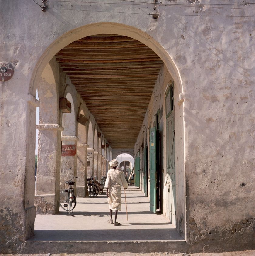 Sudan, 1958 – Man walking by stores along an arched colonnade © 2021 Todd Webb Archive