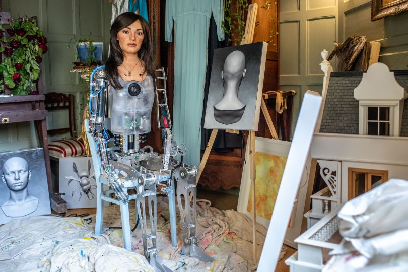 Ai-Da with her paintings. Photography by Victor Frankowski