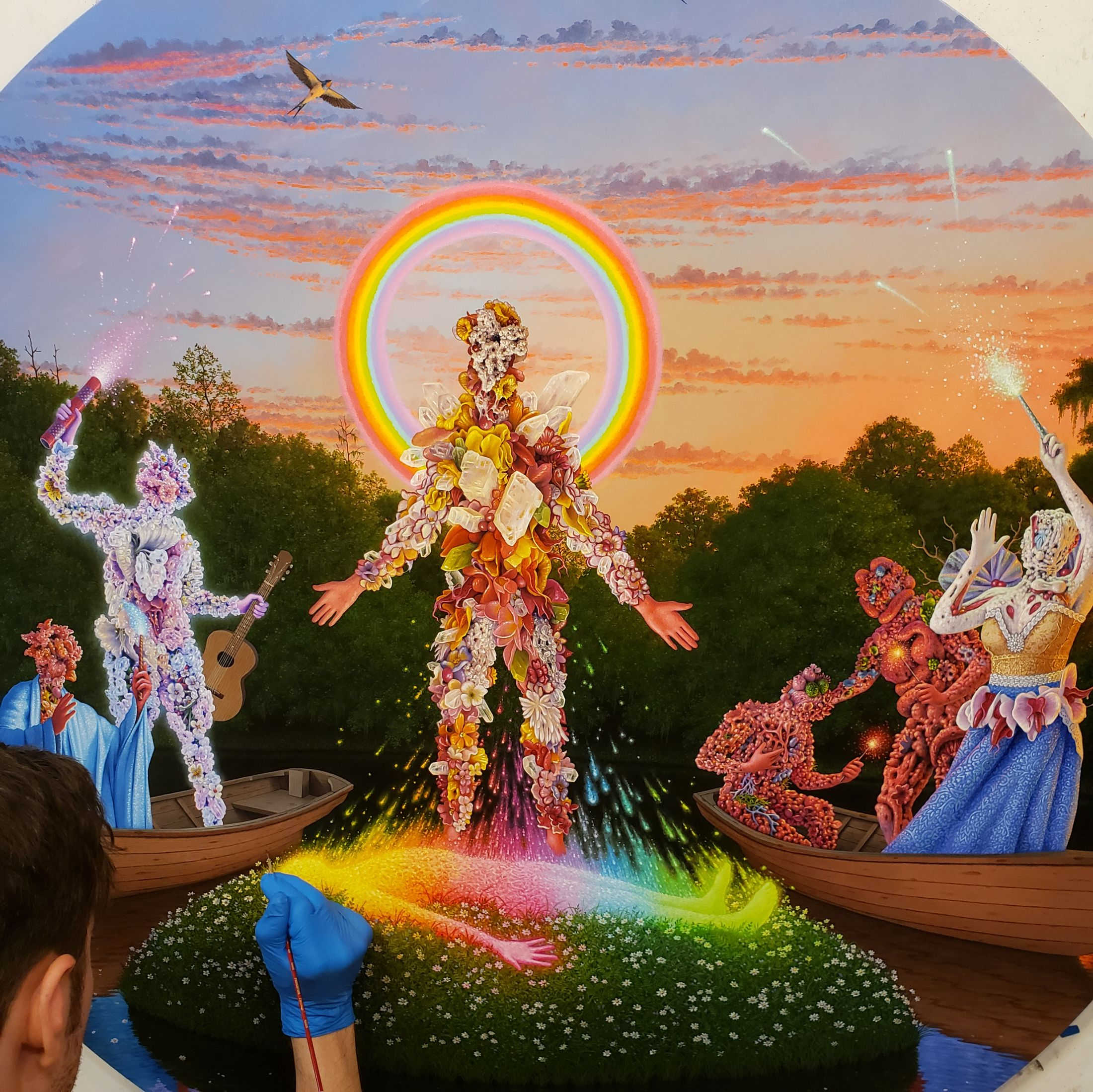 A painting of a humanoid creature whose body appears to be exposed organs and flowers, standing in a circular rainbow and performing some kind of raise-the-dead ceremony on a similar creature.