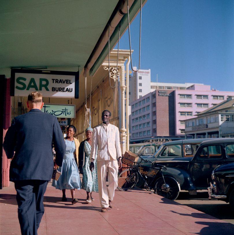 Southern Rhodesia (Zimbabwe), 1958 – Pedestrians walking past SAR Travel Bureau, Truworths, and other shops, Bulawayo © 2021 Todd Webb Archive