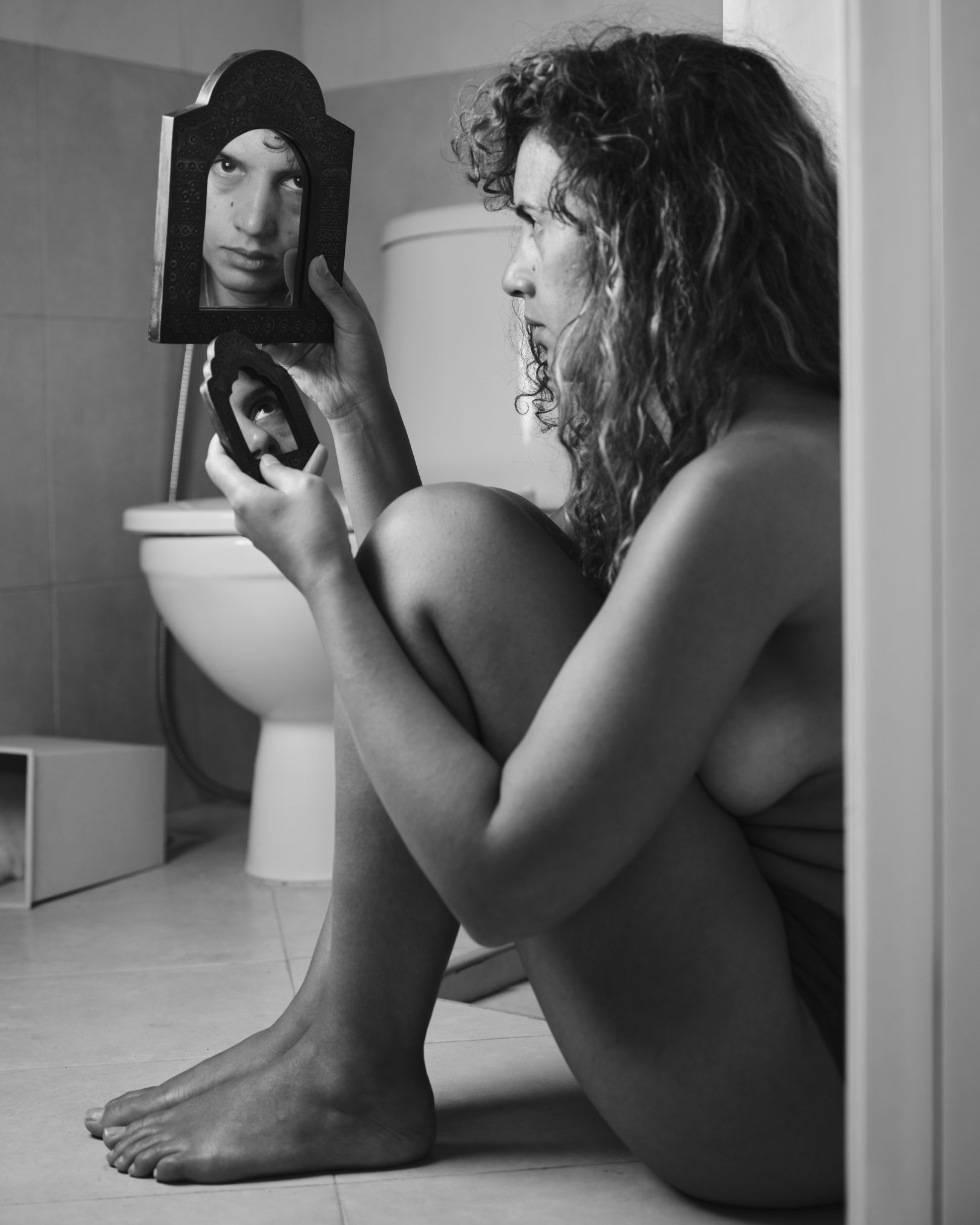 A black and white photo of a woman sitting on the bathroom floor next to her toilet. She is facing away from the camera, holding a small mirror that reflects her eyes back to the camera so she is looking at us.