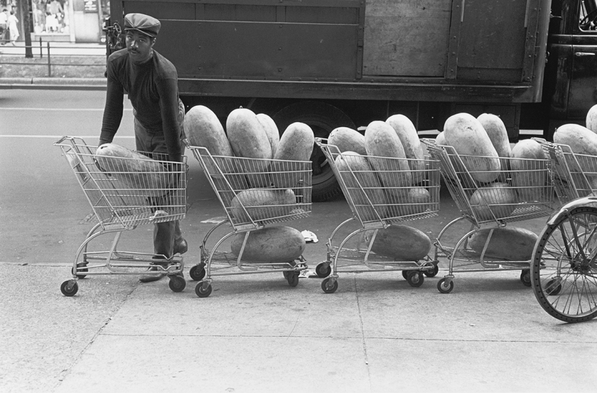 Store vendor with watermelons in shopping carts, 1966
